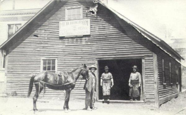 Photo taken about 1920. First blacksmith shop bought by Mr. Hugron in 1871. Elsewhere Bar site today