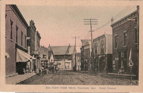 Vue dela rue Child à une époque où les rues sont encore sur la terre. Les carrioles ou voitures et chevaux sont présents. Des trottoirs de bois sont devant les commerces.